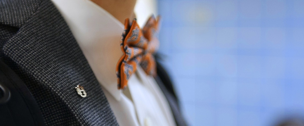 Man wearing auburn bowtie and lapel pin