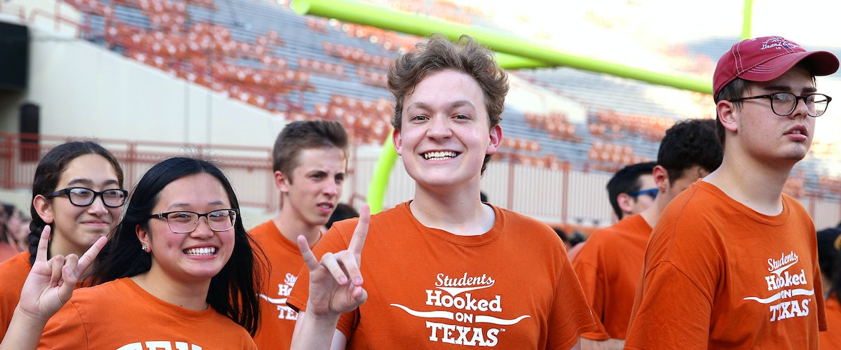 """Students showing the """"hook em"""" hand sign"""